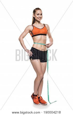 Smiling Sportswoman Wearing Sportswear And Measuring Her Waistline Isolated On White