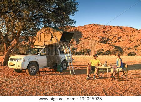 Two friends on adventure trip in desert. Happy smiling couple having a picnic meal in orange sunset light. Pickup truck with pitched roof top tent and camping equipment, table and chairs.