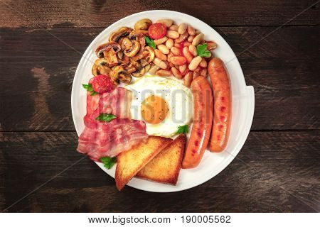 An overhead photo of a plate of English breakfast on a dark rustic texture, with a sunny side up egg, sausages, bacon, toasts, grilled mushrooms and tomatoes, and copy space