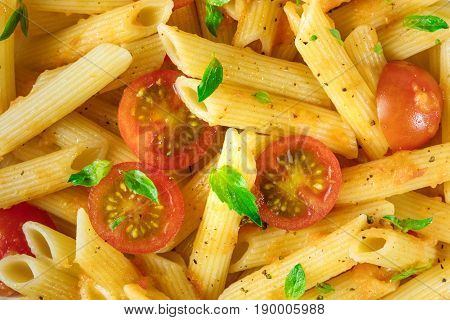 A closeup photo of a penne rigate dish, shot from above. A texture of pasta, basil leaves, and cherry tomatoes