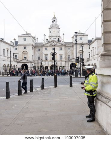 London United Kingdom 7 may 2017: policeman with walkie talkie stands guard near horse guards of london