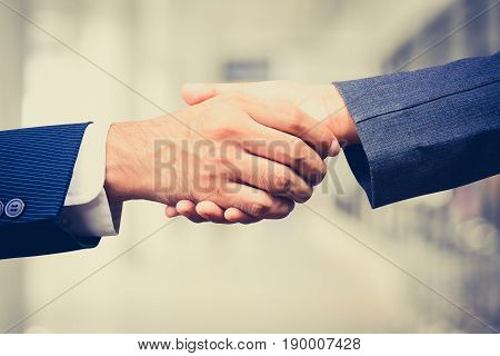 Handshake of businessman and businesswoman vintage tone - greeting dealing merger and acquisition concepts