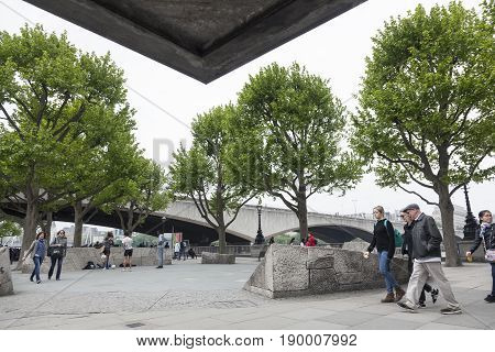 London United Kingdom 6 may 2017: people on southbank of river thames in front of national theatre near waterloo bridge on overcast day in spring