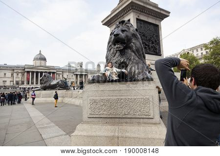 London United Kingdom 6 may 2017: tourist girl poses with lion statue on trafalgar square in london with national gallery in the background