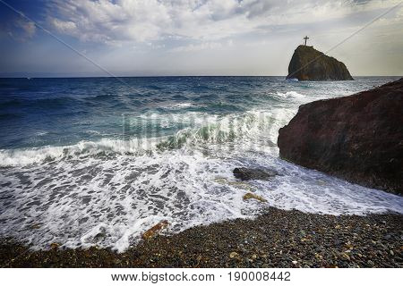 Sea waves crashing on the shore and flowing above seashore pebbles. spindrift