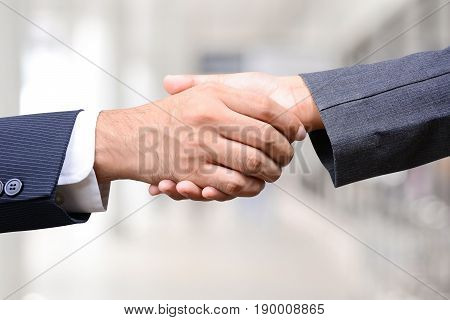 Handshake of businessman and businesswoman - greeting dealing merger and acquisition concepts