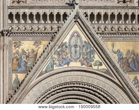 The upper part of the arch with wall paintings, mosaic, murals, spiral columns, depicting the biblical stories, Madonna, Jesus Christ, apostles, winged angels, cherubs. City of Orvieto, Italy