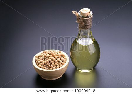 Soybeans In A Wooden Bowl And Soybean Oil On A Black Background