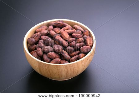 Dried Cocoa Seed In Wooden Bowl On Black Background