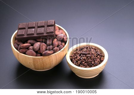 Chocolate Bar And Dried Cocoa Seed, Cocoa Nibs In Wooden Bowl On Black Background