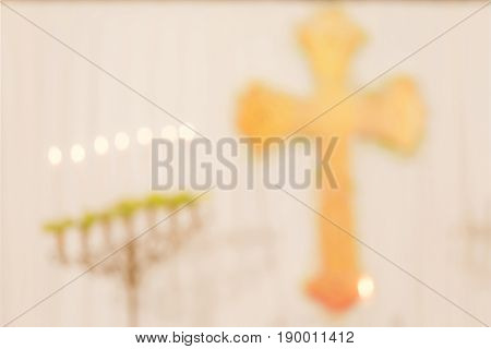 Abstract blurred photo of holy cross in white church interior decoration of wedding ceremony.