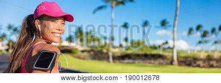 Fitness summer motivation running music woman runner run banner. Jogging Asian girl listening to smartphone app with earphones wearing cap and armband smart phone holder. Horizontal panorama crop.