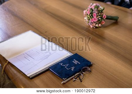 Wedding civil german marriage Register with Pen, and Bouquet of Fresh Beautiful Flowers on Top of a Wooden Table.