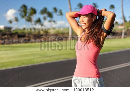 Active Asian runner woman tying hair into ponytail getting ready to run her morning jogging workout. Happy healthy lifestyle. Fitness wellness life.
