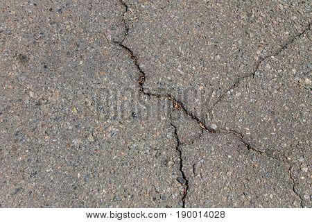 Texture with cracks on the asphalt background