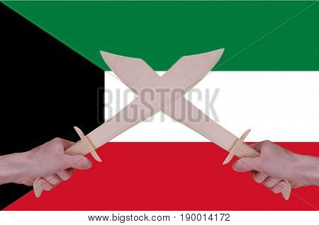 Hands hold crossed wooden sabres, Kuwait flag visible on the background.