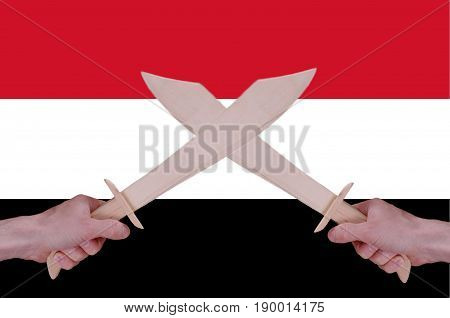 Hands hold crossed wooden sabres, Yemen flag visible on the background.