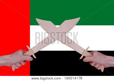 Hands hold crossed wooden sabres, United Arab Emirates flag visible on the background.