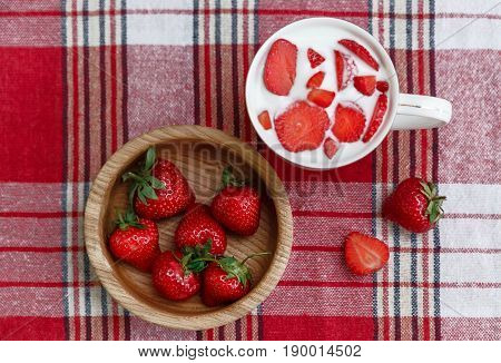 Cup of Yogurt.Red Fresh Strawberries are in the Wooden Plate on the Check Tablecloth.Breakfast Organic Healthy Tasty Food.