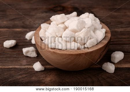Bowl of natural lump sugar on wooden background