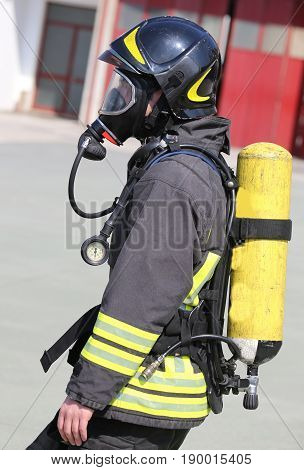 Firefighter With Large Yellow Oxygen Cylinder And Protective Hel