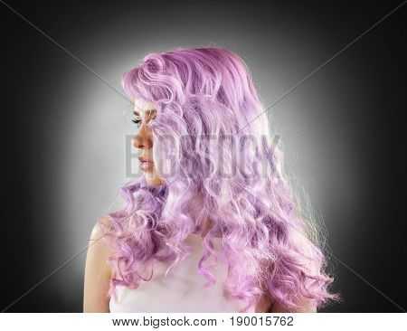 Trendy hairstyle ideas. Young woman with dyed lilac hair on dark background