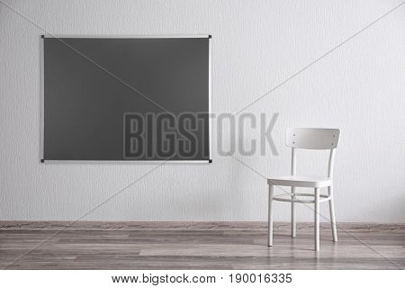 Chair and blank blackboard on wall in empty class room