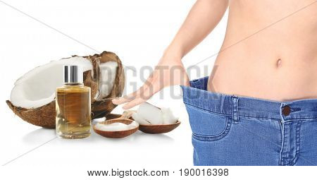 Young woman wearing big jeans on white background. Coconut oil for weight loss
