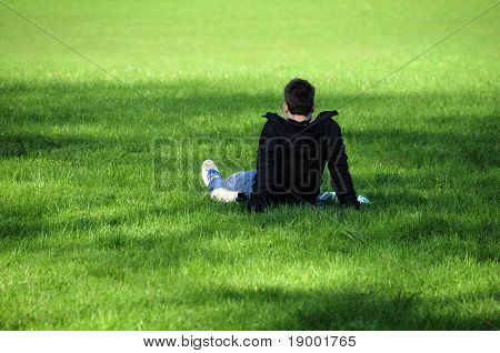 Young man relaxing on the grassy field