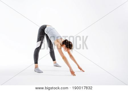 Young woman doing yoga on isolated background