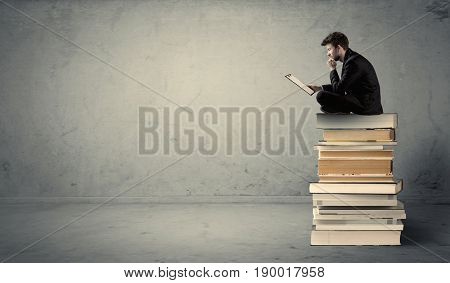 A serious businessman with tablet in hand in suit sitting on a pile of giant books in front of a textured grey wall.