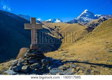 Cross in Kazbegi with view of mountain Kazbek.