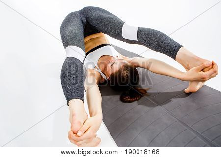 Brunette makes twine lying on rug at empty background