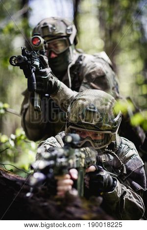 Photo of soldiers on reconnaissance in woods during day