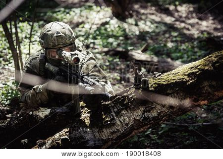 Soldier with weapons on military mission in forest
