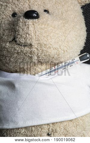 White usual toy bear with usual thermometer