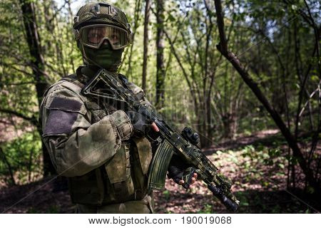Soldier in helmet on intelligence in woods by day