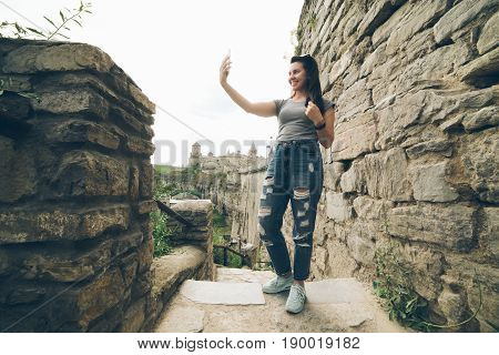 woman tasks picture in fron of old castle