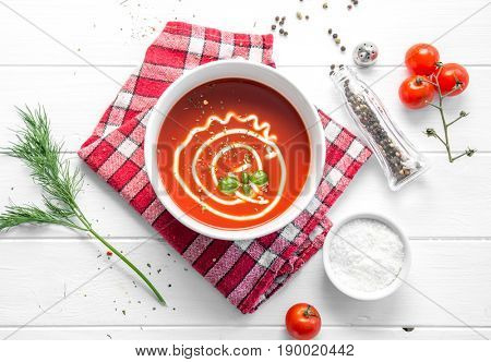Hot bowl of tomato basil soup with mayo, squared rustic napkin, salt and pepper, topview