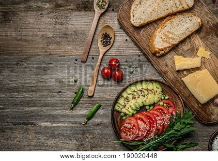 Tasty appetizers, avocado and cut tomatoes sitting on dark wooden table, topview, textspace