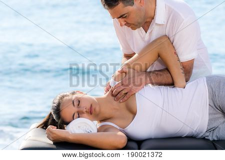 Close up portrait of male osteopath doing shoulder therapy on woman outdoors next to sea side.