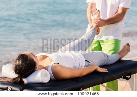 Close up of young athlete with ankle injury having curative osteopathic treatment outdoors.Girl laying on massage beg with therapist in background manipulating foot.