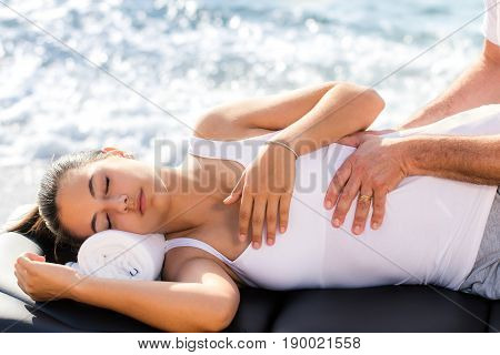 Close up of young woman having osteopathic lower back treatment outdoors next to sea side.