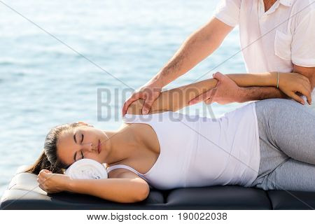 Close up of young woman at curative osteopathic shoulder therapy next to sea.