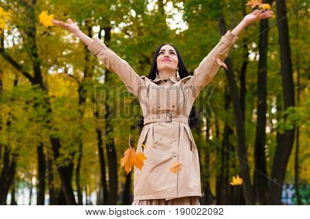 happy brunette woman throws up autumn leaves up