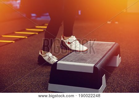 Close-up girl women Step for exercises in the gym with an athlete's foot.high contrast and monochrome color tone. Consept Weight Loss.