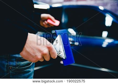 Worker holds the scraper trowel to level the surface. Concept tinting car. Toning