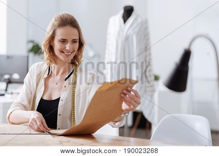 Looking content. Attractive young blond-haired woman sitting at the table, holding dress patterns and looking at them with an expression of satisfaction