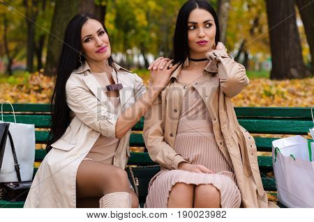 two girlfriends sitting on bench with shopping
