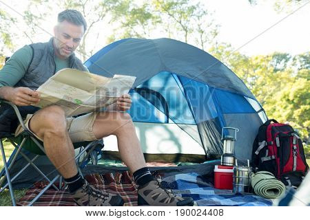 Man reading the map outside the tent at campsite